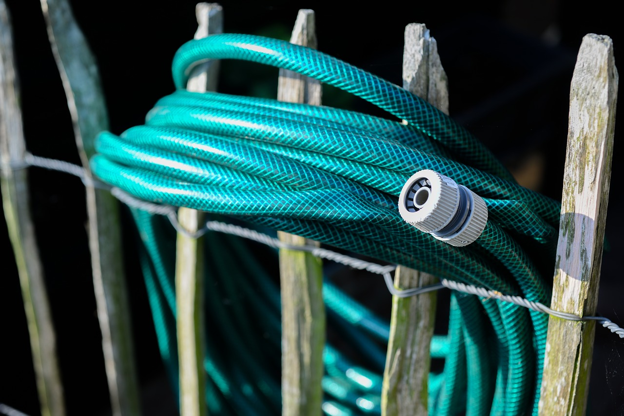 garden hose rolled and stored hanging on a fence