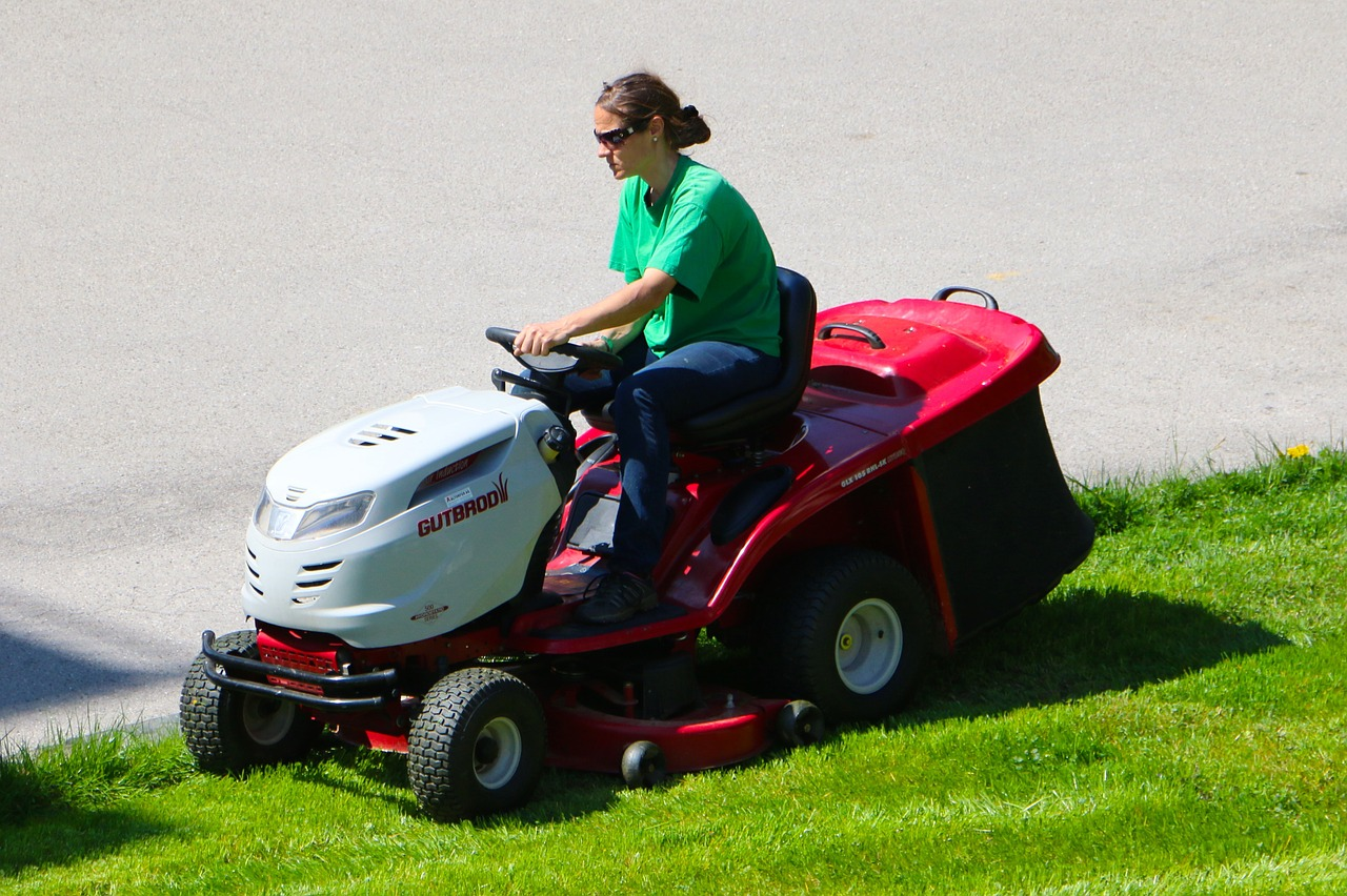 woman riding a lawn mower to trim the grass of her yard